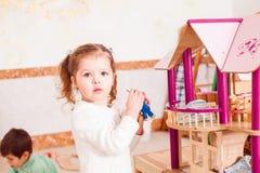 Menina que joga com uma casa de boneca imagens de stock