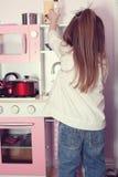 Menina que joga com uma cozinha do brinquedo Imagens de Stock Royalty Free