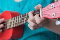Menina que joga a corda na uquelele vermelha do soprano fotografia de stock