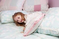 Menina que joga em sua cama Imagens de Stock