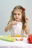 A menina que joga em uma batedeira do cozinheiro whisk os ovos em uma bacia de vidro Fotos de Stock Royalty Free
