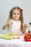 A menina que joga em uma batedeira do cozinheiro whisk os ovos em uma bacia de vidro Fotos de Stock