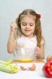 A menina que joga em uma batedeira do cozinheiro whisk os ovos em uma bacia de vidro Foto de Stock