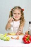A menina que joga em uma batedeira do cozinheiro whisk os ovos em uma bacia de vidro Foto de Stock Royalty Free
