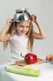 Menina que joga no cozinheiro psto sobre um colander sobre sua cabeça Imagens de Stock Royalty Free