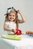 Menina que joga no cozinheiro psto sobre um colander sobre sua cabeça Imagem de Stock Royalty Free