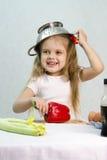 Menina que joga no cozinheiro psto sobre um colander sobre sua cabeça Foto de Stock Royalty Free