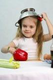 Menina que joga no cozinheiro psto sobre um colander sobre sua cabeça Fotografia de Stock