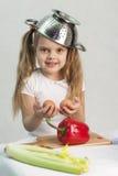Menina que joga no cozinheiro psto sobre um colander sobre sua cabeça e posses nas mãos os ovos Fotos de Stock