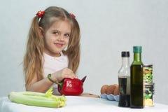 A menina que joga em um cozinheiro corta a pimenta vermelha da faca Foto de Stock