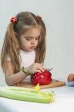 A menina que joga em um cozinheiro corta a pimenta vermelha da faca Fotos de Stock