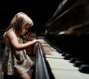 Menina que joga em um piano. Imagens de Stock