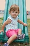 Menina que joga em uma corrediça Fotografia de Stock