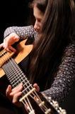 Menina que joga a guitarra acústica Fotografia de Stock
