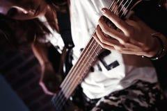Menina que joga a guitarra-baixo interna na sala escura fotos de stock royalty free
