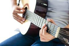 Menina que joga a guitarra - mão do foco Imagem de Stock