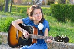 Menina que joga a guitarra na natureza Fotos de Stock Royalty Free