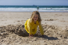 Menina que joga na areia na praia Imagem de Stock