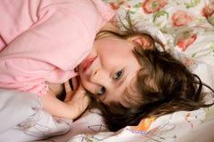 Menina que joga na cama Fotografia de Stock Royalty Free