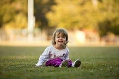 Menina que joga na grama, rindo Fotos de Stock