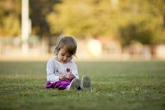 Menina que joga na grama, rindo Imagens de Stock