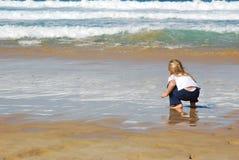 Menina que joga na praia imagem de stock royalty free