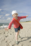 Menina que joga na praia Imagem de Stock