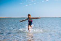 Menina que joga na praia bonita do oceano imagem de stock