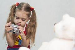 A menina toma a foto da câmara digital da peluche Fotografia de Stock