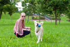 Menina que joga no parque com um filhote de cachorro Foto de Stock