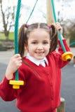 Menina que joga no quadro de escalada no campo de jogos da escola Foto de Stock