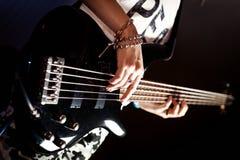 Menina que joga o fim interno da guitarra-baixo acima Fotografia de Stock Royalty Free
