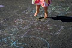 Menina que joga o hopscotch Foto de Stock