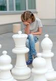 Menina que joga o jogo de xadrez Fotos de Stock