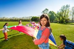 Menina que joga o jogo do paraquedas no campo verde Imagens de Stock Royalty Free