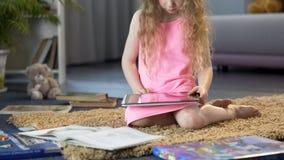 Menina que joga o jogo educacional interativo na tabuleta, usando o app móvel fotos de stock