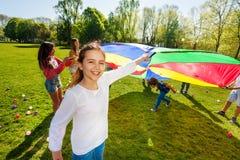 Menina que joga o paraquedas junto com seus amigos Foto de Stock Royalty Free