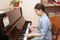 A menina que joga o piano Imagens de Stock