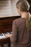 Menina que joga o piano Foto de Stock