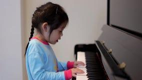 Menina que joga o piano video estoque