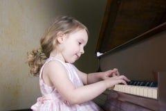 Menina que joga o piano Fotos de Stock Royalty Free