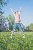 Menina que joga o salto da aro do hoola- Fotografia de Stock Royalty Free