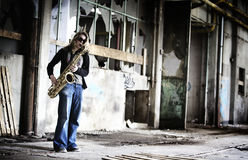 Menina que joga o saxofone no salão velho da fábrica. Fotografia de Stock Royalty Free
