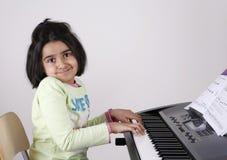 Menina que joga o teclado Imagens de Stock