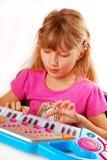Menina que joga o teclado de piano Foto de Stock