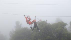 Menina que joga o zipline na névoa Fotografia de Stock Royalty Free