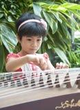Menina que joga o zither Foto de Stock Royalty Free