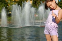 Menina que joga pela fonte de água Fotografia de Stock