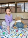 Menina que joga serpentes e escadas com Teddy Bear Fotos de Stock Royalty Free