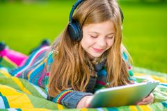 Menina que joga a tabuleta em um parque Imagens de Stock Royalty Free